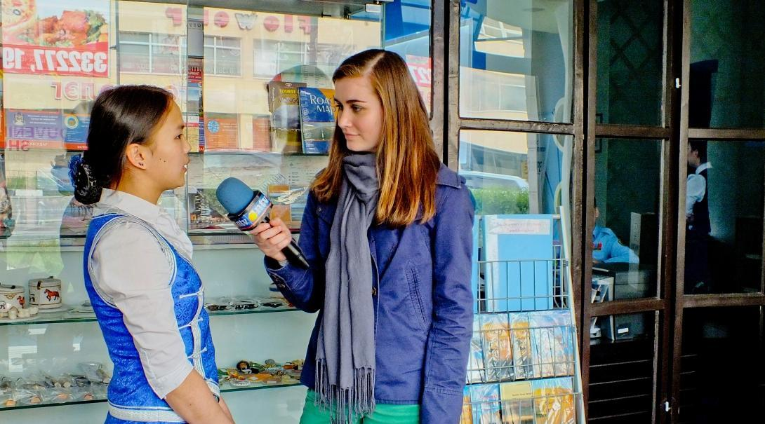 A journalism intern in Mongolia speaks to a woman in the street